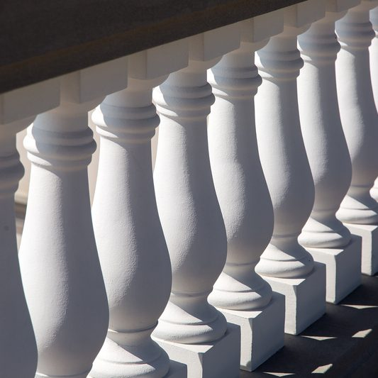 white baluster stone balusters closeup of an architectural structure lit by sunlight.